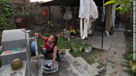 Maya washes her clothes outside the home of a family that has given her a new life in Kathmandu.