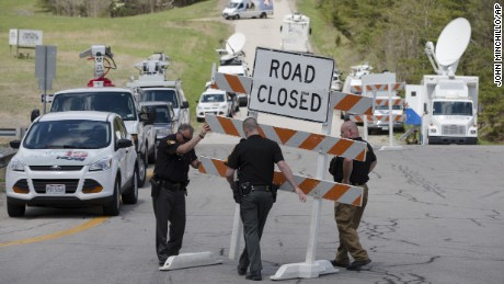 Authorities set up road blocks at the intersection of Union Hill Road and Route 32 at the perimeter of a crime scene, Friday, April 22, 2016, in Pike County, Ohio. Shootings with multiple fatalities were reported along a road in rural Ohio on Friday morning, but details on the number of deaths and the whereabouts of the suspect or suspects weren't immediately clear. The attorney general's office said a dozen Bureau of Criminal Investigation agents had been called to Pike County, an economically struggling area in the Appalachian region some 80 miles east of Cincinnati. (AP Photo/John Minchillo)
