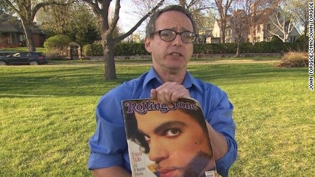 Journalist and author, Neal Karlen, holds up a copy of a Rolling Stone article he wrote about Prince.