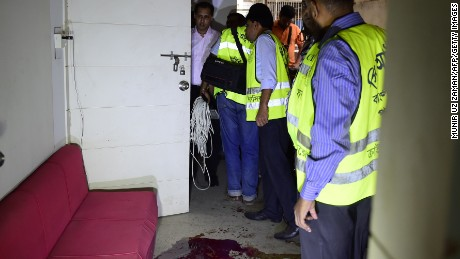 Bangladeshi police examine the scene of an attack on a publisher on October 31, 2015.