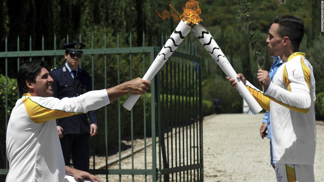 Petrounias passed the Olympic flame to a second torchbearer on April 21 -- Brazilian volleyball player, Giovane Gávio (L).