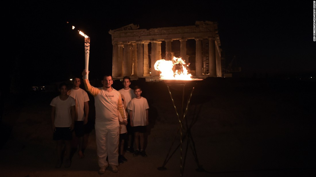 Greek former Olympic weightlifting gold medalist Pyros Dimas also held the torch, and stands here atop the Acropolis hill by the the ancient temple of the Parthenon, after lighting a cauldron with the Olympic flame.