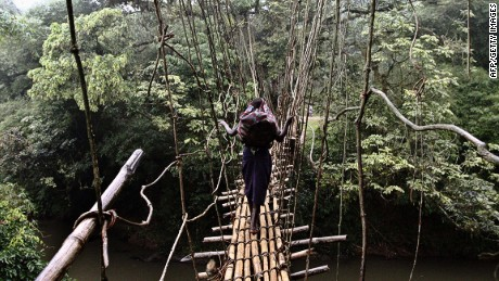A young girl walks on a makeshift bridge made out of bamboo near the town of Luvungi, Congo to get to a nearby market.