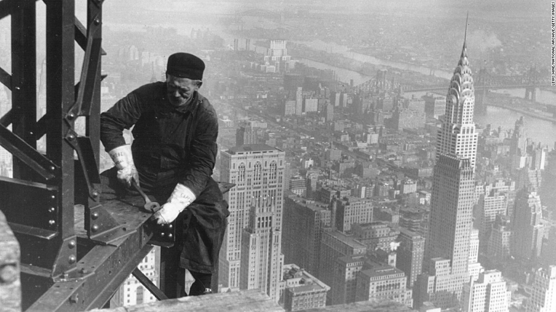 A worker sits on a beam during the construction of the Empire State Building. Construction began on March 17, 1930, with 3,000 workers building 4.5 floors per week.