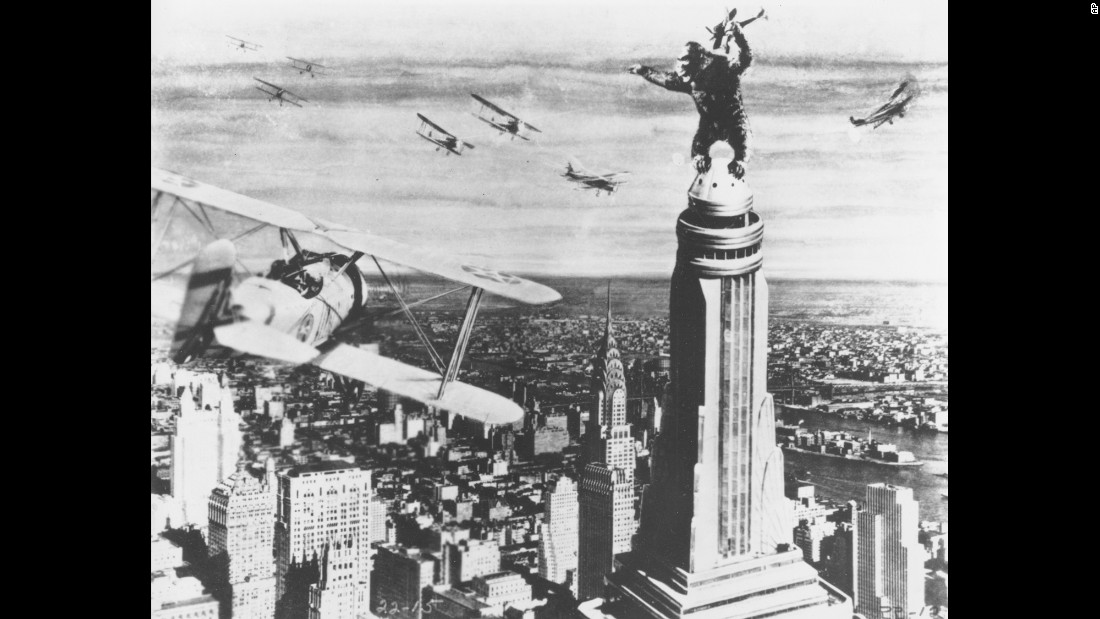 "King Kong stands atop the Empire State Building as he holds an airplane during an attack by fighter planes in a scene from the film ""King Kong."" The movie was released on May 2, 1933."