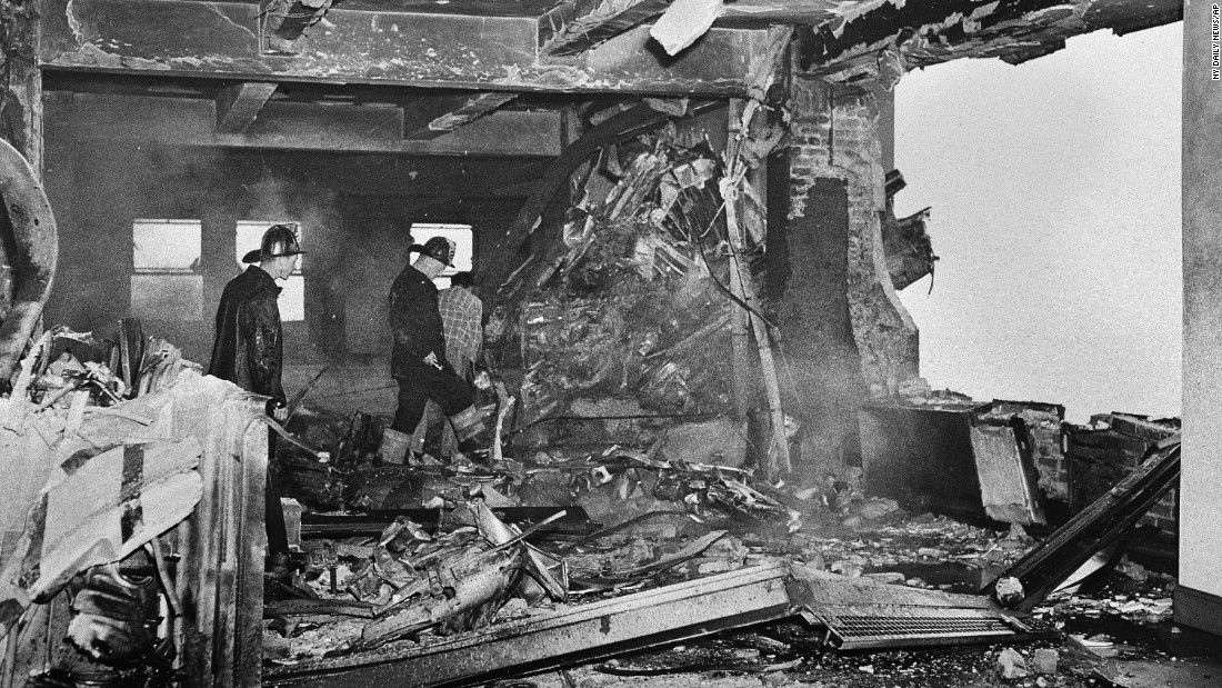 "Firefighters search through the charred ruins near the gaping hole in the wall of an office on the 79th floor of the Empire State Building in New York, on July 28, 1945. An Army Air Corps B-25 twin-engine bomber plane crashed into the building due to foggy conditions. <a href=""http://www.npr.org/templates/story/story.php?storyId=92987873"" target=""_blank"">Two stories were damaged, and 14 people are killed.</a>"