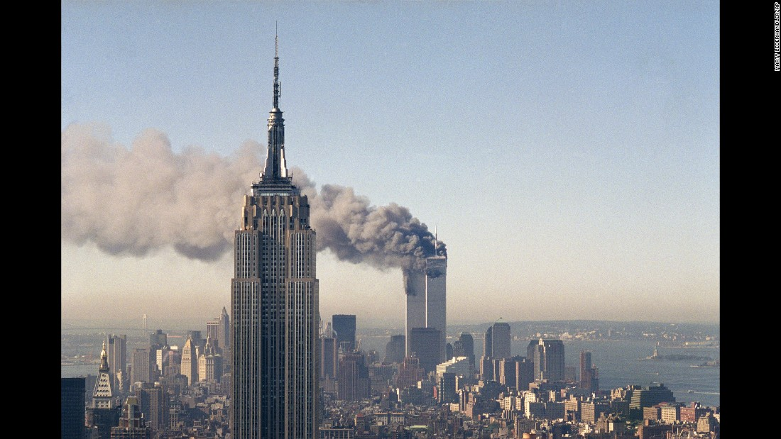 "The twin towers of the World Trade Center burn behind the Empire State Building in New York, on <a href=""http://www.cnn.com/2013/07/27/us/september-11-anniversary-fast-facts/"" target=""_blank"">September 11, 2001</a>."