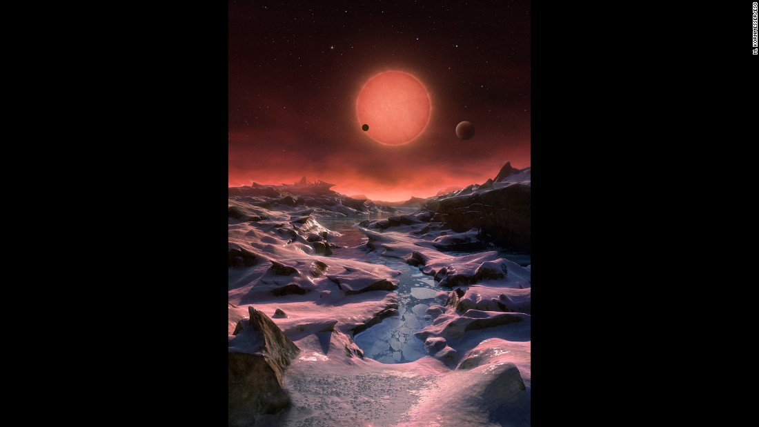 This artist's impression shows an imagined view from the surface one of the three planets orbiting an ultracool dwarf star just 40 light-years from Earth that were discovered using the TRAPPIST telescope at ESO's La Silla Observatory. Given the proximity of the dwarf star, the rosy sun would appear very large in the sky.