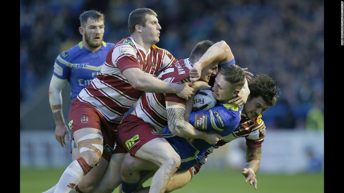 Ben Currie of the Warrington Wolves is gang-tackled by Wigan players during a Super League match in Warrington, England, on Thursday, April 28.