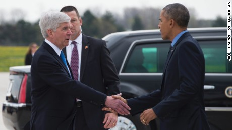 US President Barack Obama shakes hands with Michigan Governor Rick Snyder upon his arrival at Bishop International Airport in Flint, Michigan, May 4, 2016.
