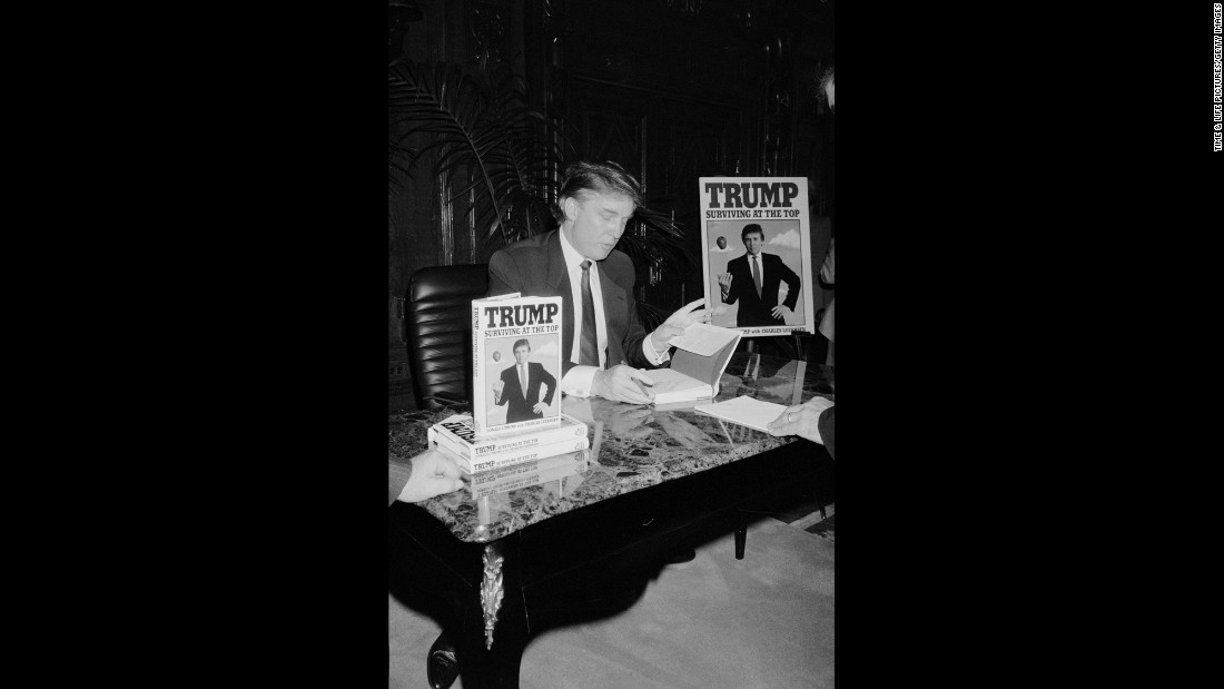 "Trump signs his second book, ""Trump: Surviving at the Top,"" in 1990. Trump <a href=""http://www.trump.com/publications/"" target=""_blank"">has published</a> at least 16 other books, including ""The Art of the Deal"" and ""The America We Deserve."""