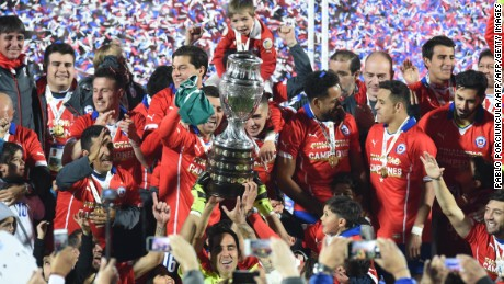 Chilean players celebrate with the trophy of the 2015 Copa America football championship, in Santiago, Chile, on July 4, 2015.    AFP PHOTO / PABLO PORCIUNCULA        (Photo credit should read PABLO PORCIUNCULA/AFP/Getty Images)