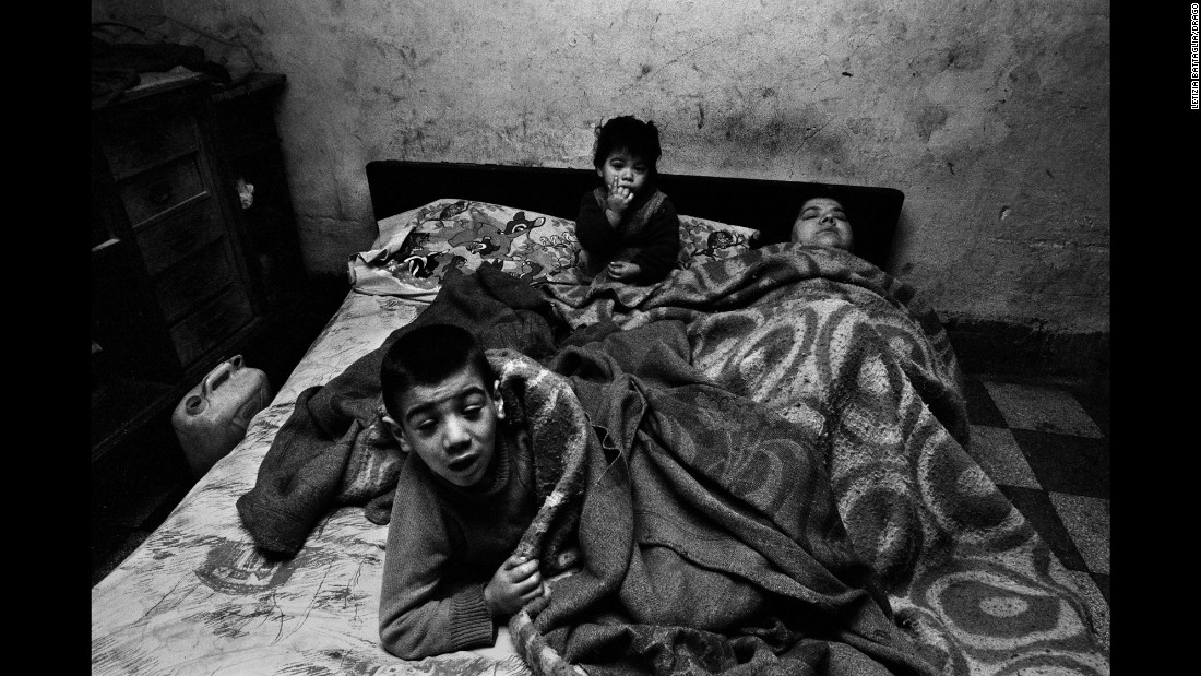 "A woman and her children are photographed in Palermo in 1978. ""I was shooting poor people, and I entered a house around noon,"" Battaglia said. ""I asked her, 'Why are you in bed at this hour?' and she said, 'I have no fire, no light, no food ... what can I do?' People brought her spaghetti, but she was always in bed with the children. I always wondered what happened to this woman and those children."""