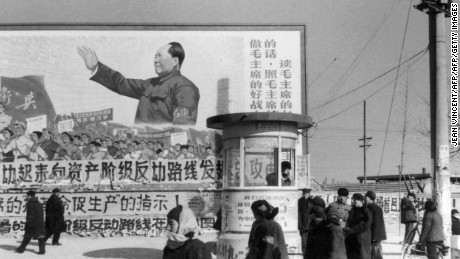 "A small group of Beijing residents walk in February 1967 in downtown Beijing, past a huge poster showing the Chairman Mao Zedong, during the ""Great Proletarian Cultural Revolution"". The poster reads (at right): ""We have to be good soldiers of Mao Zedong, we have to listen his words, we have to follow his instructions and read his books"".  Since the the cultural revolution was launched in May 1966 at Beijing University,  Mao's aim was to recapture power after the failure of the ""Great Leap Forward"". The movement was directed against those ""party leaders in authority taking the capitalist road"".        (Photo credit should read JEAN VINCENT/AFP/Getty Images)"
