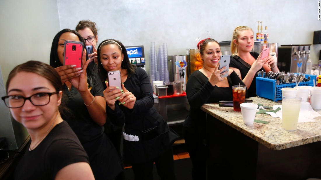 Waitresses take photographs of Democratic presidential candidate Hillary Clinton during a campaign stop in Indianapolis on Sunday, May 1.