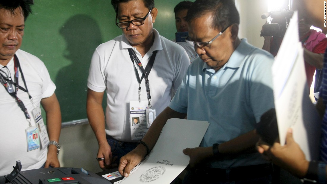 Presidential candidate and current Philippine Vice President Jejomar Binay (right) inserts his ballot into the vote counting machine inside a polling center at the San Antonio National High School in Makati, Philippines on May 9, 2016.
