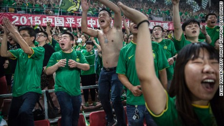 BEIJING, CHINA - JUNE 28: (CHINA OUT) Ultra supporters and fans of the Beijing Guoan FC celebrate together after a goal against Chongcing Lifan FC during their Chinese Super League match on June 28, 2015 in Beijing, China. There are growing legions of ardent supporters and fans of China's football clubs. The government is also trying to foster a football culture in the country by mandating football programs in 20,000 Chinese schools in a recent plan devised by President Xi Jinping to make China a football power. (Photo by Kevin Frayer/Getty Images)
