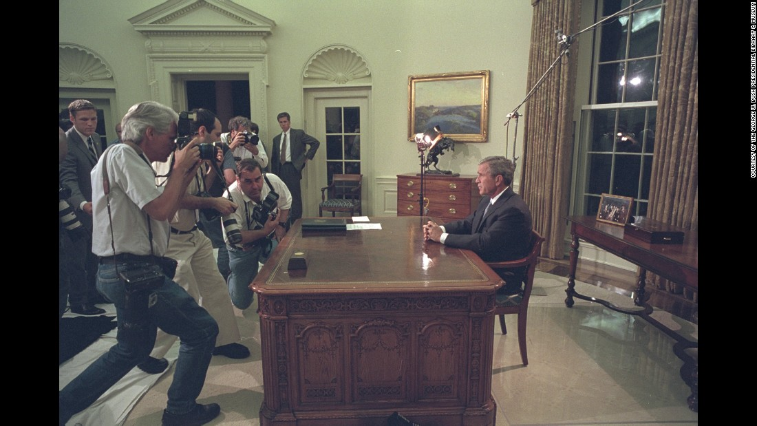 Bush pauses for members of the press before addressing the nation from the Oval Office.