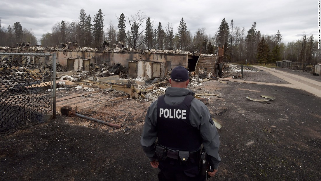 A police officer looks over a destroyed building in the Abasands neighborhood of Fort McMurray on Monday, May 9.
