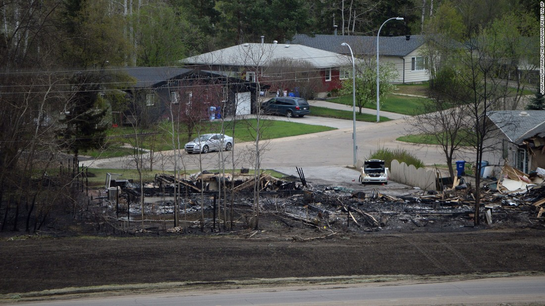 Remains of a burned-out house sit near intact homes in Fort McMurray on May 9.