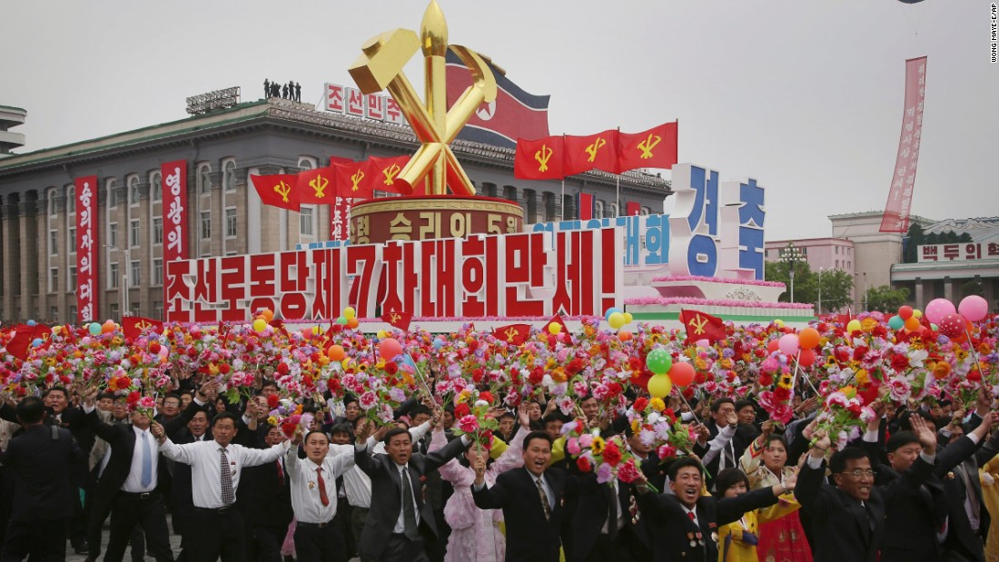 "North Koreans march with the Workers' Party symbol and the words under it which read ""Long Live the 7th Congress of the Workers' Party of Korea."""