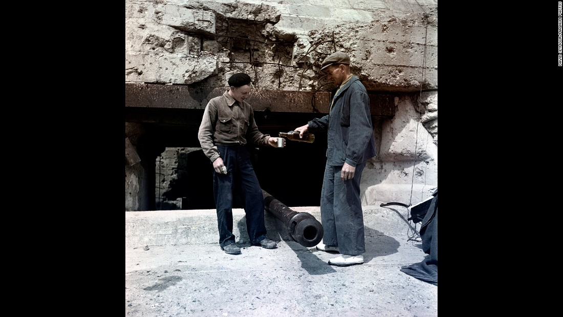 Two men share a drink at Omaha Beach in 1947. V-E Day was announced 71 years ago this week, ending the European phase of World War II.