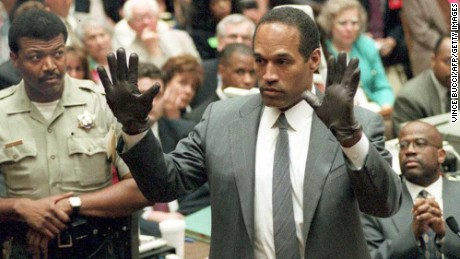 LOS ANGELES, CA - JUNE 21:  O.J. Simpson shows the jury a new pair of Aris extra-large gloves, similar to the gloves found at the Bundy and Rockingham crime scene 21 June 1995, during his double murder trial in Los Angeles,CA. Deputy Sheriff Roland Jex(L) and Prosecutor Christopher Darden (R) look on.