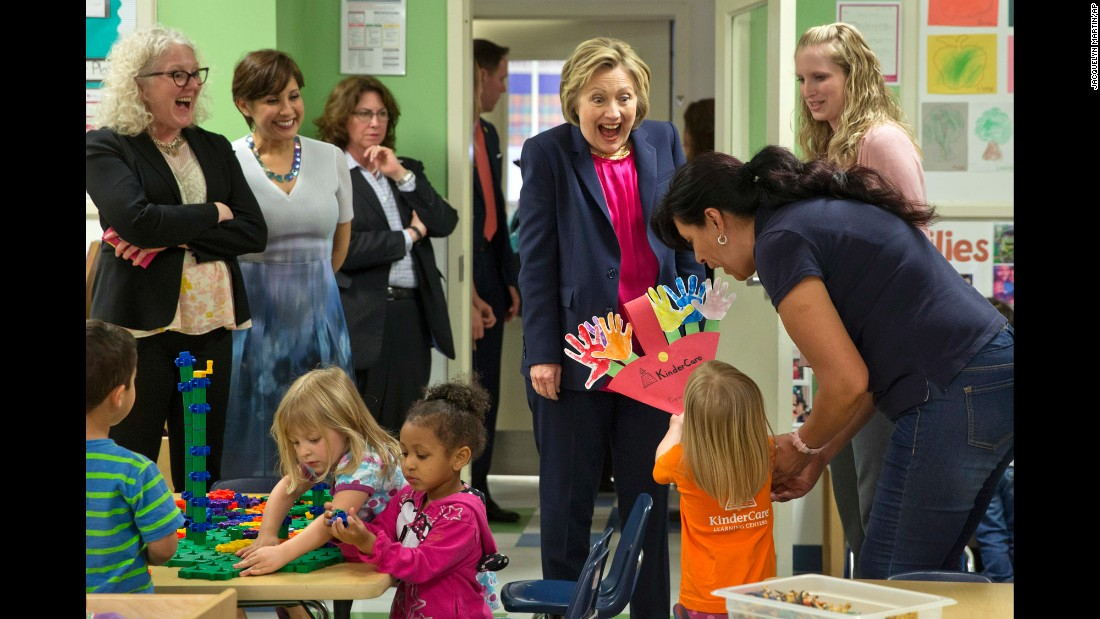 Democratic presidential candidate Hillary Clinton reacts as a 3-year-old presents her with artwork at a day-care center in Fairfax, Virginia, on Monday, May 9.