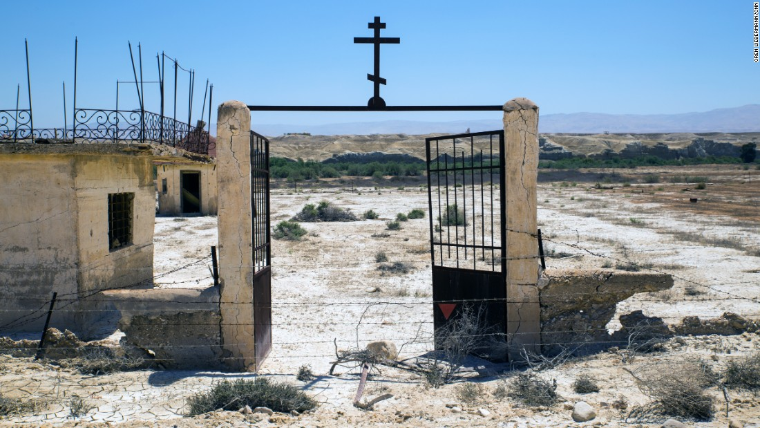 The rusted gate of the Russian Orthodox church looks out onto the Jordan River and the Jordanian mountains beyond. After the fields are cleared, each church will have its own walking path to the river.