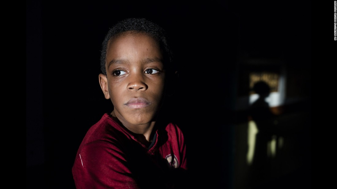 Hussein, 7, poses for a portrait. He's a brother of Essa in the first photo.