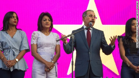 Danilo Medina (2nd-R), presidential candidate of the Party of Dominican Liberation, accompanied by his wife Candida Montilla (2nd-L), speaks to supporters at the party's headquarters in Santo Domingo on May 16, 2016.  Medina appeared set Monday to win re-election by a landslide in the Dominican Republic, capitalizing on an economic boom in the Caribbean tourist paradise despite the fact that millions still live in poverty. / AFP / afp / Erika Santelices        (Photo credit should read ERIKA SANTELICES/AFP/Getty Images)