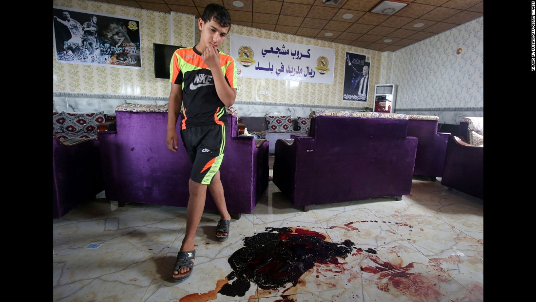 A boy walks past bloodstains and debris at a cafe in Balad, Iraq, that was attacked by ISIS gunmen on May 13, 2016. Twenty people were killed.