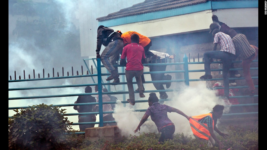 "Opposition supporters climb over a fence into the University of Nairobi campus as they flee from clouds of tear gas fired by riot police. ""The protests started a couple weeks ago, and have been taking place every Monday outside the offices of the electoral commission."" Curtis said."
