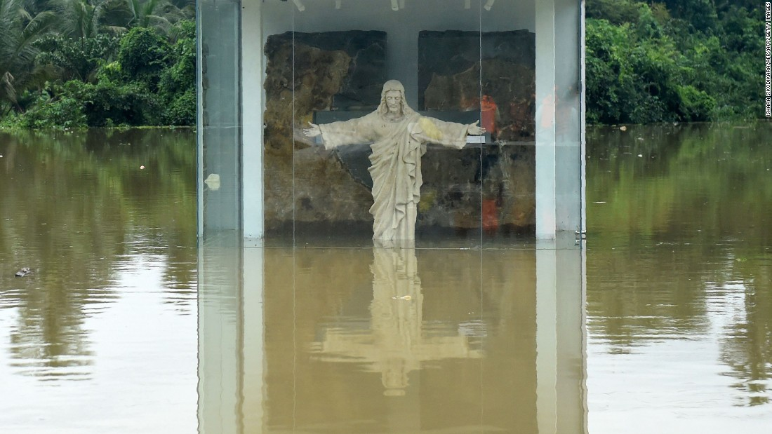 A roadside statue of Jesus Christ is submerged by floodwaters in Pugoda, about 35 km (22 mi) from Colombo on May 17.