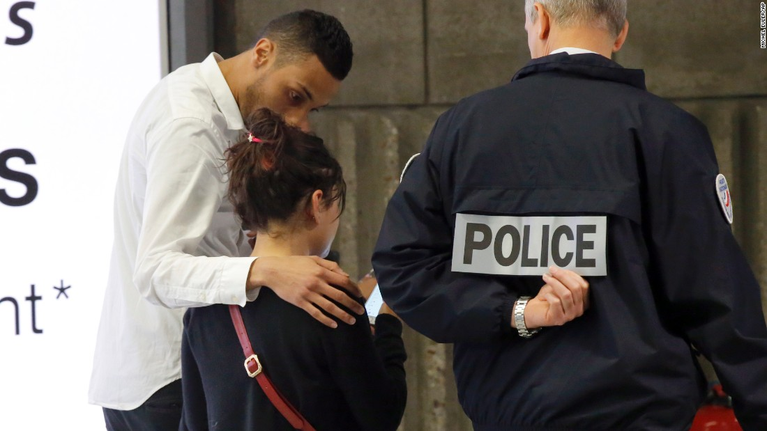 A relative is escorted at Paris' Charles de Gaulle Airport.