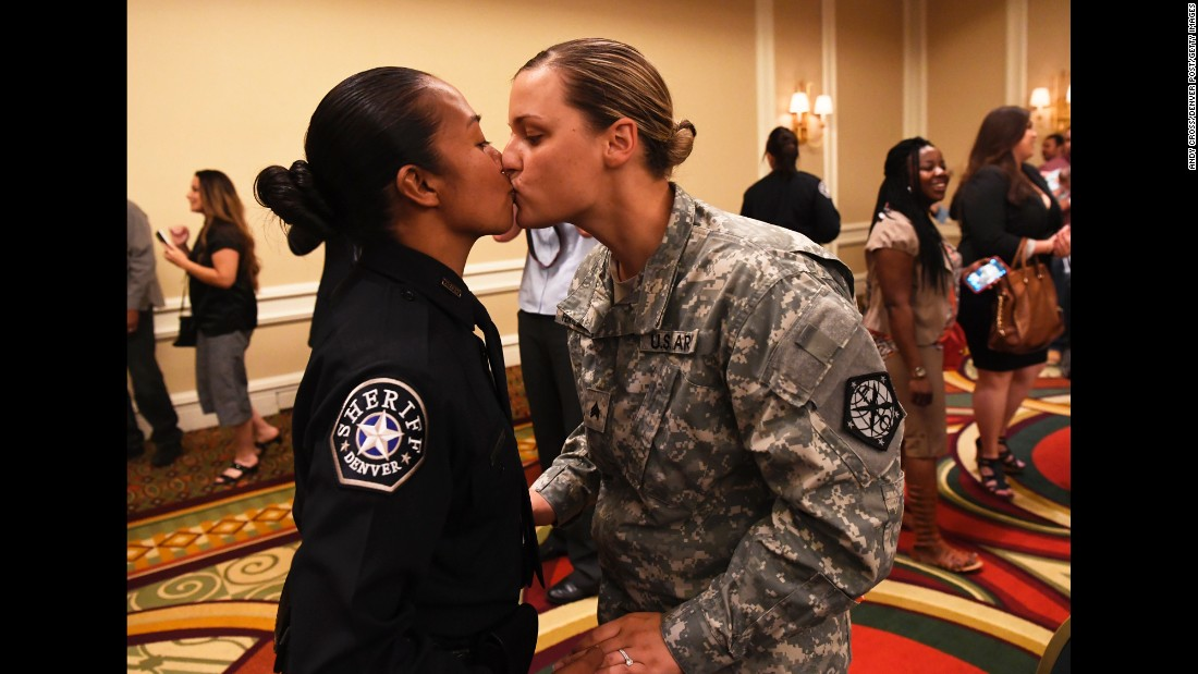 U.S. Army Sgt. Kathryn Fermin-Weinreb, right, kisses her wife, Victoria, after Victoria graduated from the Denver Sheriff Department's training academy on Friday, May 13.