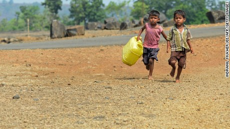 Children run with containers towards a well to collect their supply of potable water following a tanker's daily delivery in Shahapur on May 13, 2016.