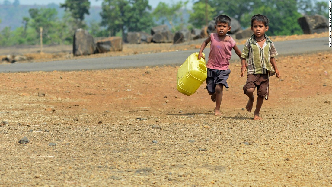 Children run with containers toward a well in Shahapur, India, on May 13 2016.