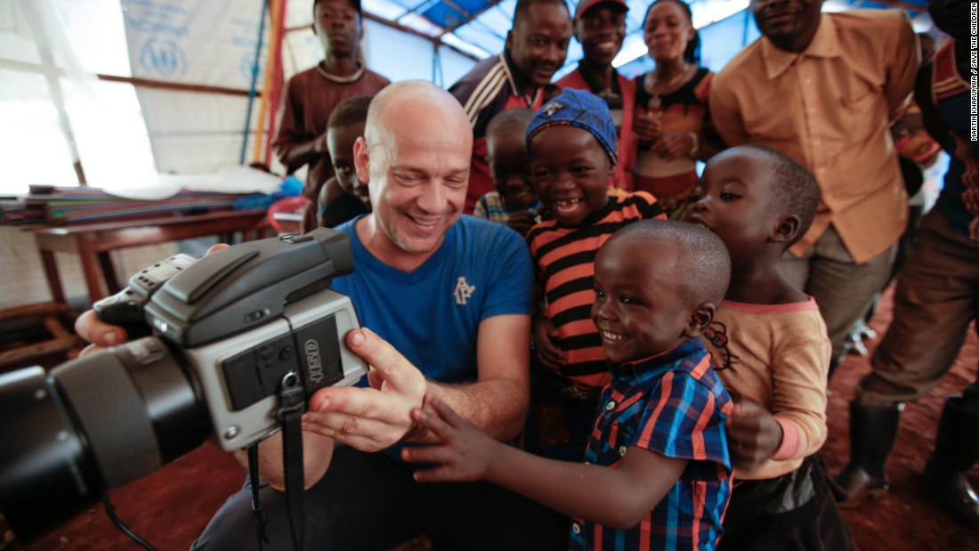 Photographer Patrick Willocq shares a preview of one of his photos with the children and carpenters who helped him create the image in the Nyarugusu camp for Burundian refugees in Tanzania.
