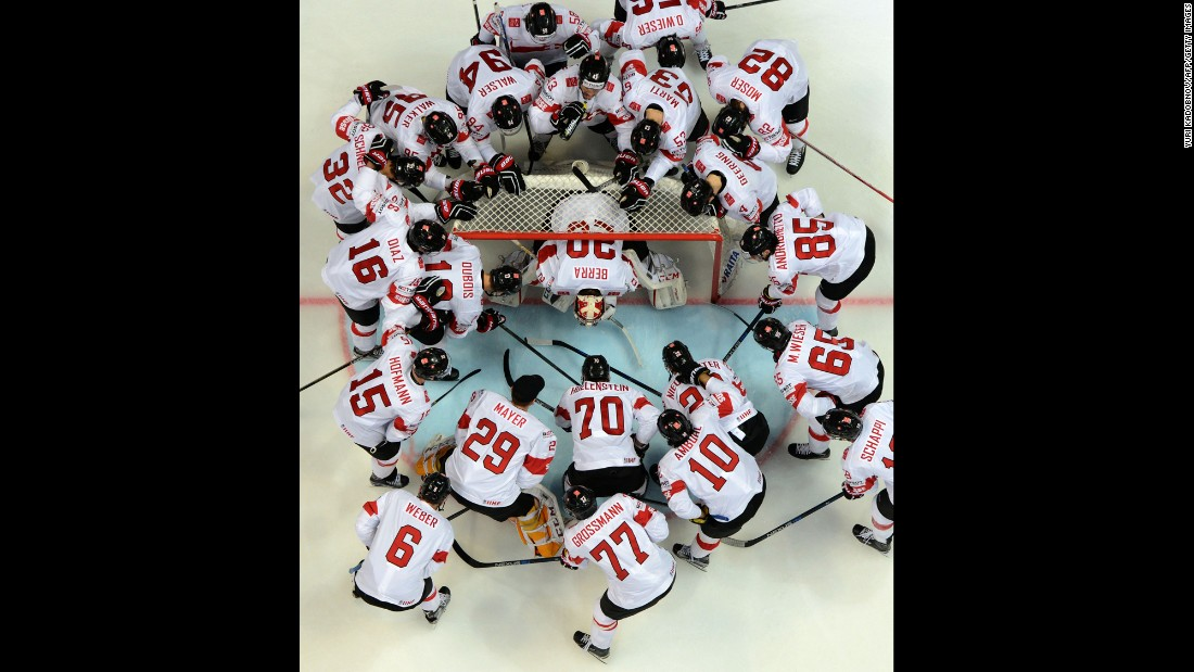 Swiss hockey players surround goalie Reto Berra before a game at the World Championships on Tuesday, May 17.