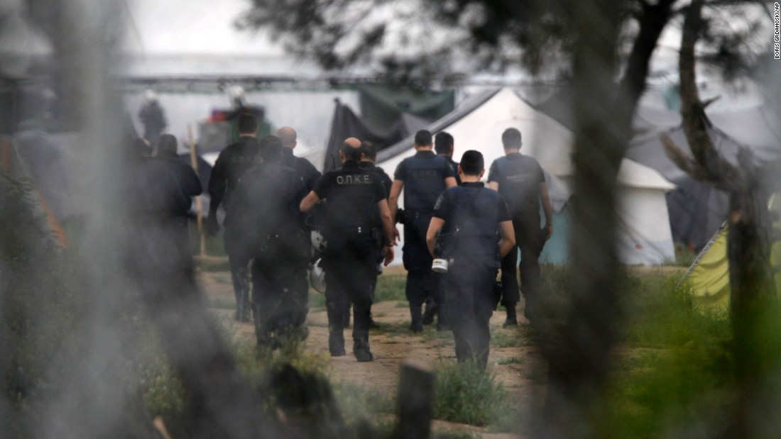Greek policemen walk into a makeshift camp at the Greek-Macedonian border near the northern village of Idomeni on Tuesday, May 24.