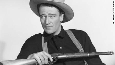 John Wayne holding a rifle in a publicity photo for the movie Shepherd of the Hills.