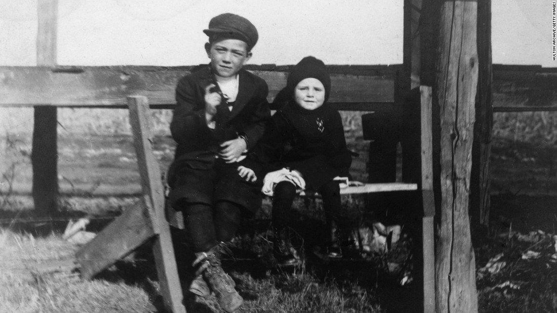 "Wayne, left, sits with his younger brother Robert in this photo circa 1915. Wayne was born as Marion Morrison in Winterset, Iowa, but he preferred to go by his nickname ""Duke"" -- which was started by firefighters who always saw him with his Airedale dog of the same name. He would later take the name John Wayne for his acting career."