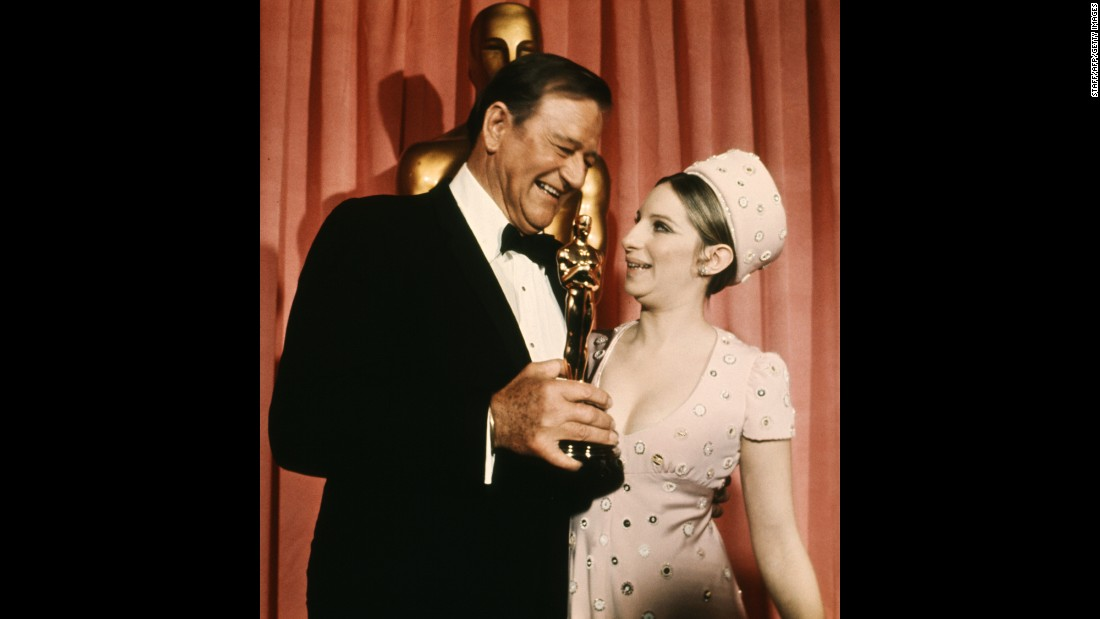"Wayne stands next to actress Barbra Streisand after winning the best actor Oscar in 1969. He won the award for his role as U.S. Marshal Rooster Cogburn in ""True Grit."" ""Ladies and gentleman, I'm no stranger to this podium,"" he said in <a href=""https://www.youtube.com/watch?v=7qQhODwivLU"" target=""_blank"">his acceptance speech.</a> ""I've come up here and picked up these beautiful golden men before, but always for friends. ... I feel very grateful, very humble."""