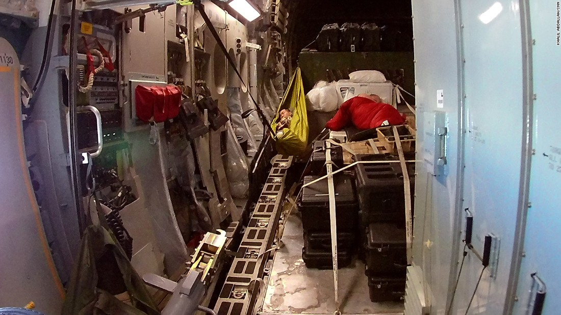 One military member finds a cozy spot to sleep in the back of the plane during the flight.