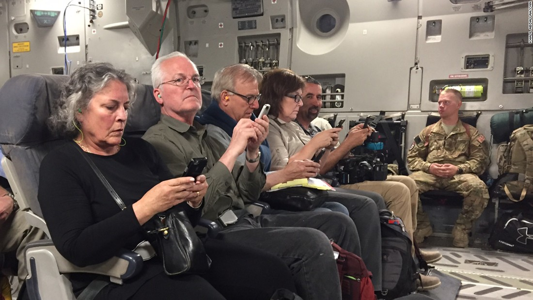 Journalists send one last email on the plane before taking off to return home.