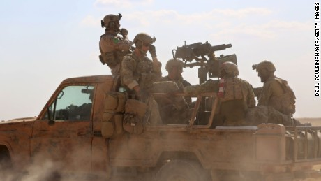 TOPSHOT - Armed men in uniform identified by Syrian Democratic forces as US special operations forces ride in the back of a pickup truck in the village of Fatisah in the northern Syrian province of Raqa on May 25, 2016.