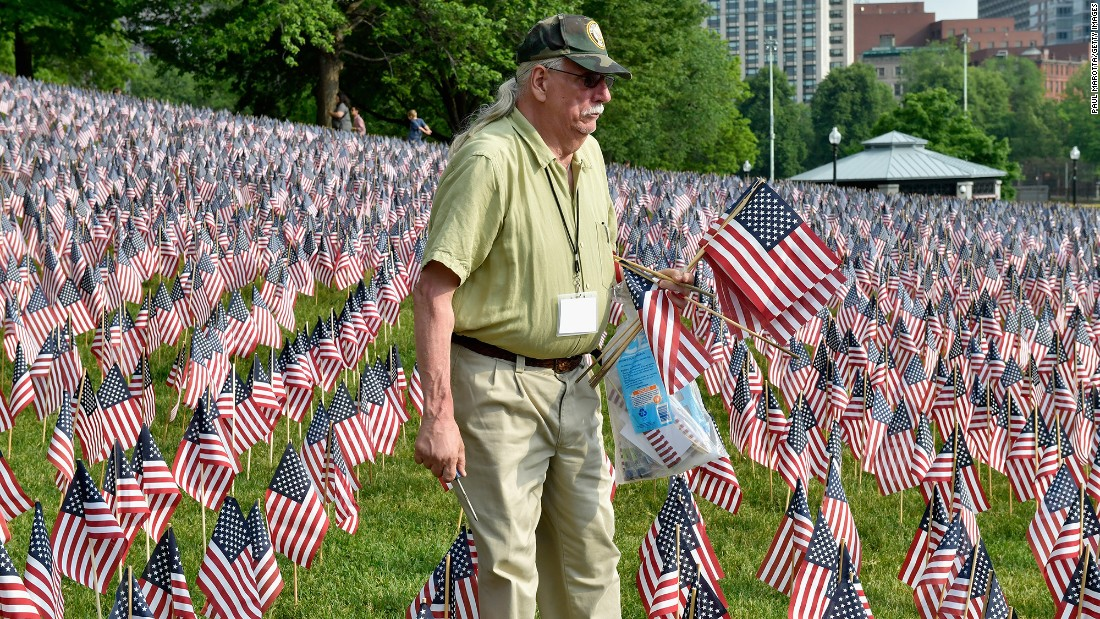 "Volunteer Robert Sherman tends to the ""garden"" of 37,000 American flags planted on Boston Common for Memorial Day weekend. Each flag represents a Massachusetts resident killed in combat."