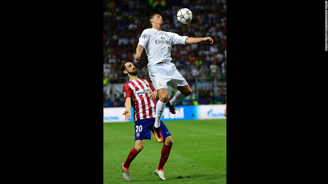 Real Madrid forward Cristiano Ronaldo heads the ball next to Atletico Madrid defender Juanfran.