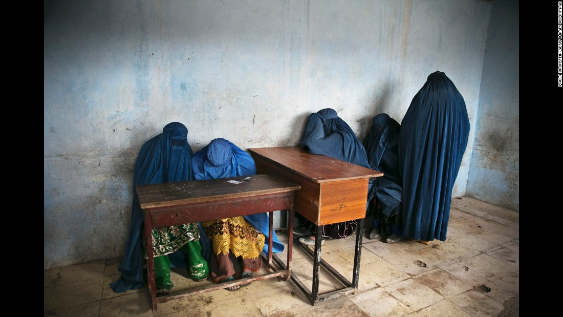 Burqa-clad women wait to vote after ballot papers ran out at a polling station in Kabul in April 2014.